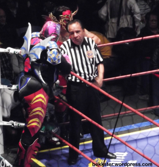 "The ref talking with the ""rudos"", the wrestlers who fight dirty. The ""técnicos"" are the goody-two-shoes who follow all the rules."