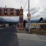 Riding under an archway decorated for a festival near San Nicolas de los Ranchos